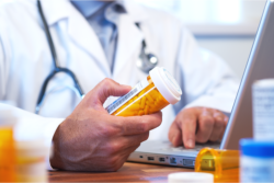 a pharmacist's hand holding a bottle of medicine